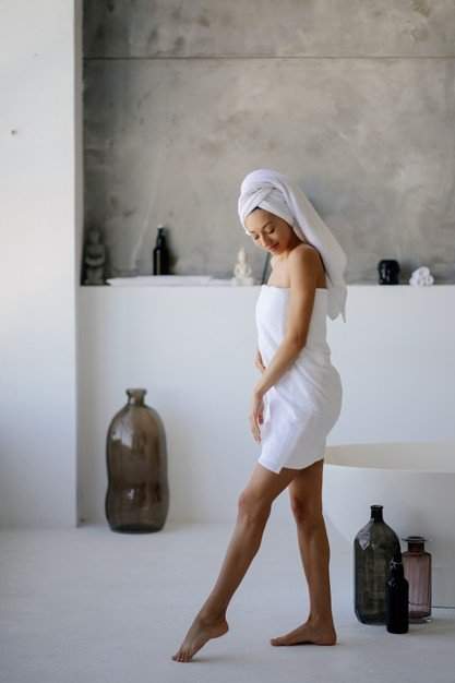 relaxed-young-female-model-white-towel-feels-refreshed-after-taking-shower_1153-7363